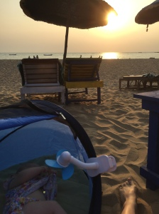 Baby on holiday in a pop-up tent travel cot on a beach in Goa, with the sun setting over the sea. A mini fan is keeping the baby cool. There are sun loungers on the beach.