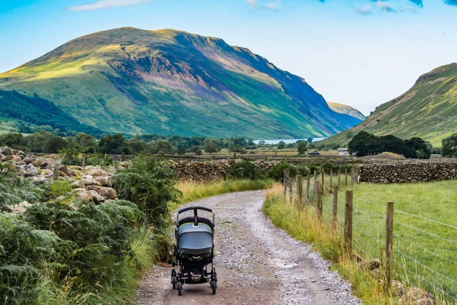 A pushchair with a sleeping baby in it on a country road in the mountains