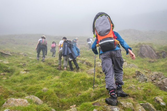 A family climbs a mountain in the Lake District, the man in the foreground of the picture carrying a toddler in a baby carrier backpack.