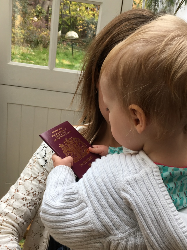 A baby in its mother's arms holds a new British passport