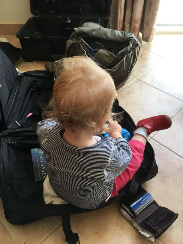 A toddler sits in an open suitcase, other bags on the floor around her.