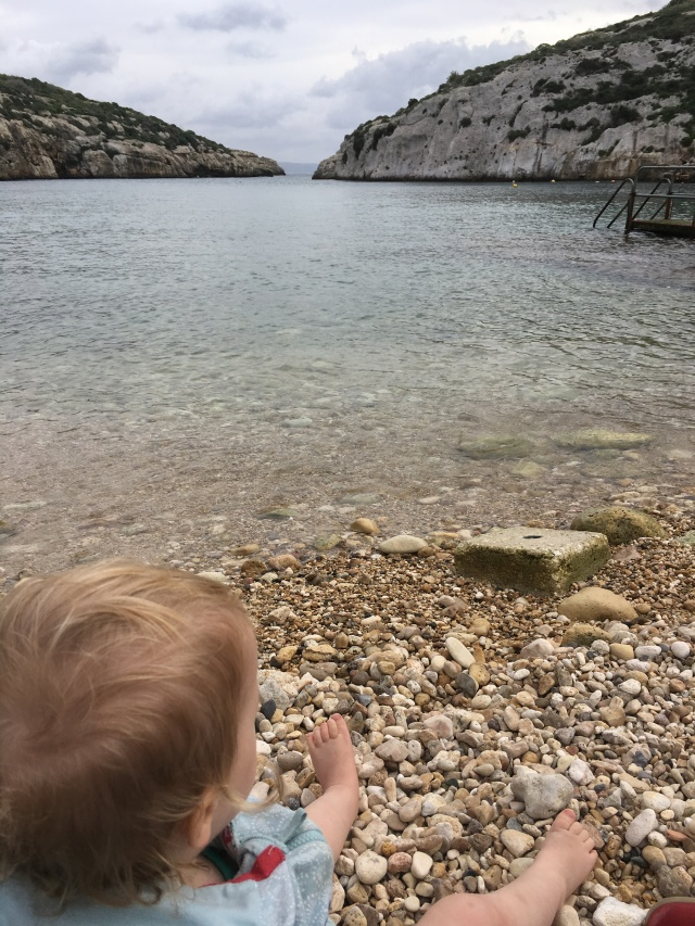 A blonde baby sits on a pebbly beach, looking out over a bay with crystal clear water