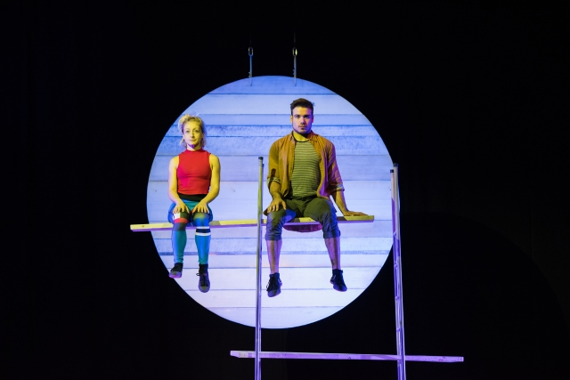 A man and a woman balance on a plank suspended through a ladder, in front of a theatre set of a moon.