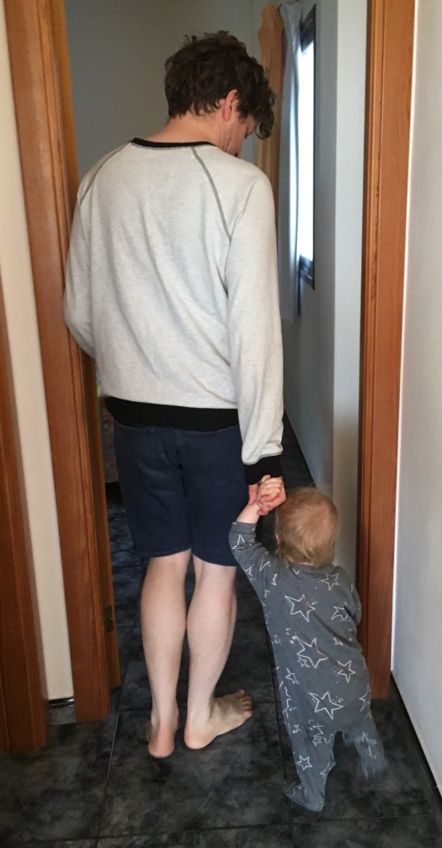 A man and a baby walk down a tiled corridor in an apartment.
