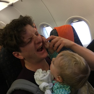 A baby grabs her father's face on a plane