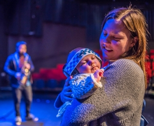 A smiling mother holds a newborn baby wearing ear defenders in an empty theatre, while a man plays saxophone in the background. Credit Steve Pretty