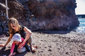 A woman and a baby play on a black sand beach