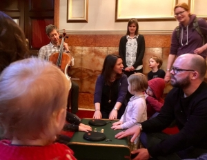 Small children and adults gathered around a suitcase listen to a cello