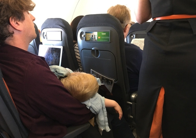 A man sleeps with a sleeping baby on his lap while a flight attendant passes