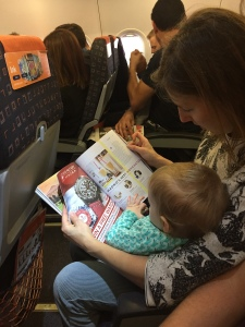 A mother and child look at a magazine on a plane