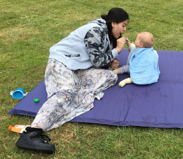 A woman feeds a baby on a blanket on grass