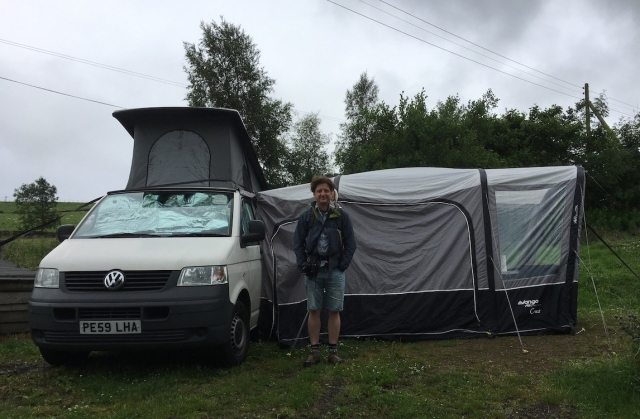 A man with a baby in a back carrier stands in front of a white camper van and awning