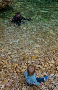 A baby sits on the beach watching a scuba diver come out of the sea