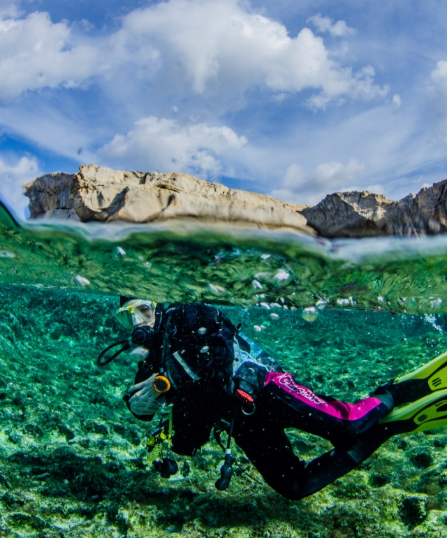 A scuba diver in shallow water, with Crocodile Rock in the background