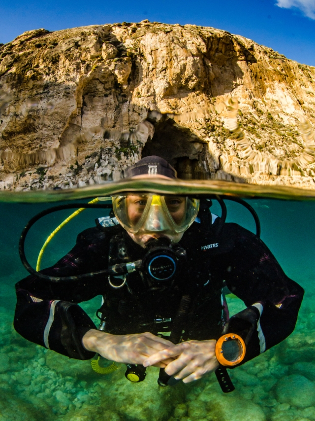 A scuba diver is photographed in front of a channel through a cliff in Gozo