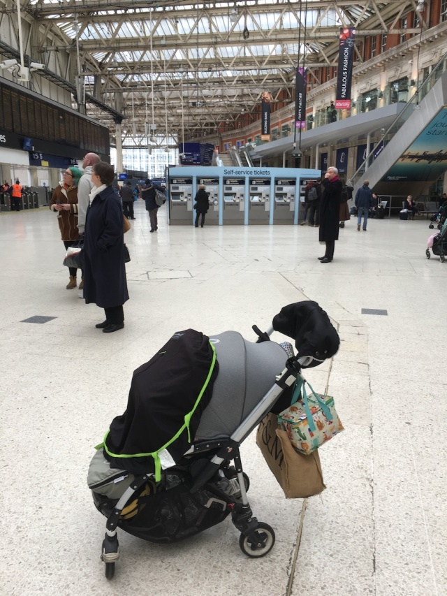 A pushchair covered with a SnoozeShade on the concourse at Waterloo Station
