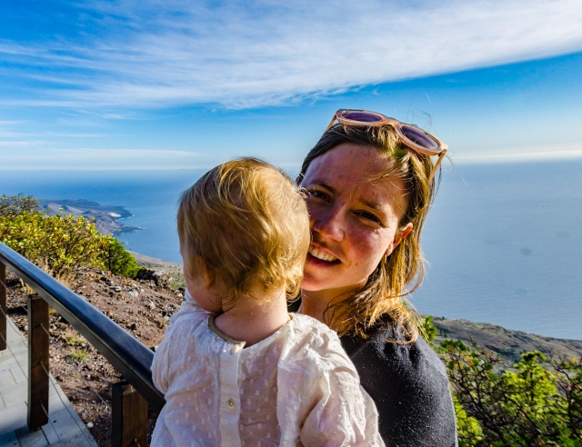 A woman holds a baby in the afternoon sunshine. In the background is the beautiful view of the coastline of El Hierro from the visitor centre at El Julan © Steve Pretty