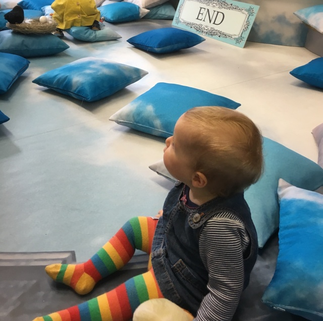 A baby girl sits on stage at the end of a performance for babies
