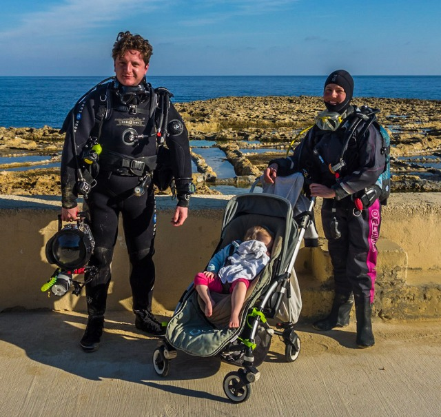 A man and a woman in scuba gear stand at the seaside with their daughter in a pushchair