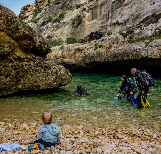 Scuba divers come out of the sea while a baby watches on a beach