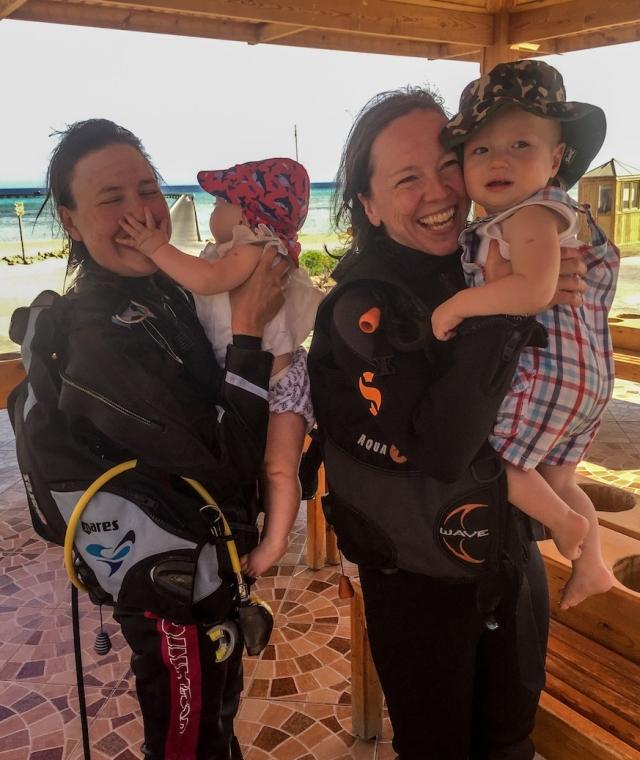 Two women in scuba dive gear hold babies wearing sun hats