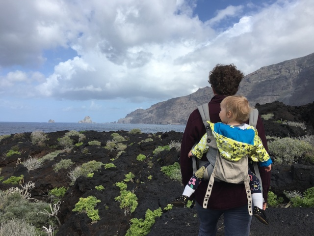 A man hikes through a volcanic seaside landscape with a baby on his back on El Hierro in the Canary Islands