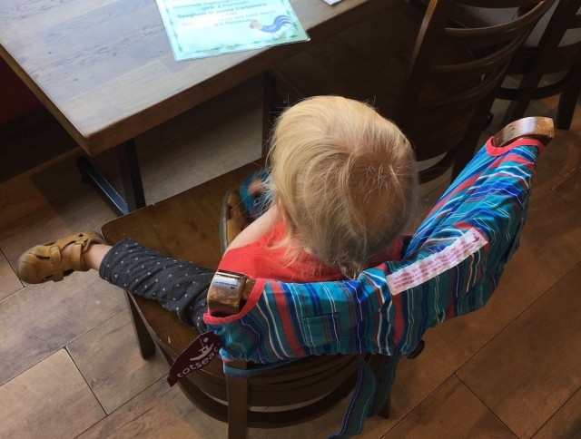 Toddler in a portable high chair at a table in a restaurant