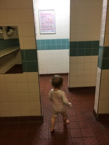 A toddler in a swimming pool changing room