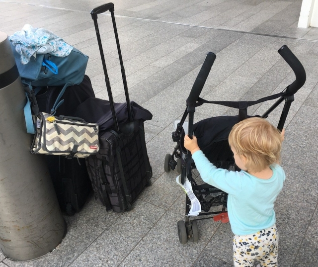 A toddler pushes a buggy next to a pile of luggage