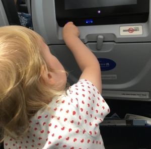 A toddler plugs in a phone charge on a plane