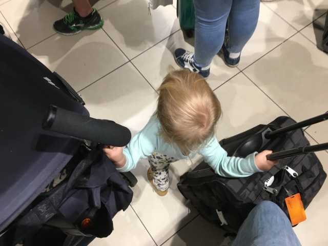 A toddler stands in a queue with a buggy and a wheelie bag