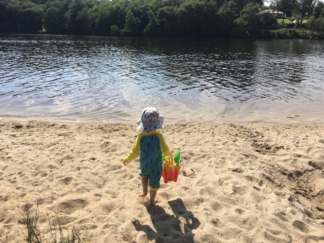 A toddler on a beach at a lake in a 'grow-with-me' sun hat from Twinklebelle and UV rash guard swim vest and shorts from Jan & Jul, the company's other brand
