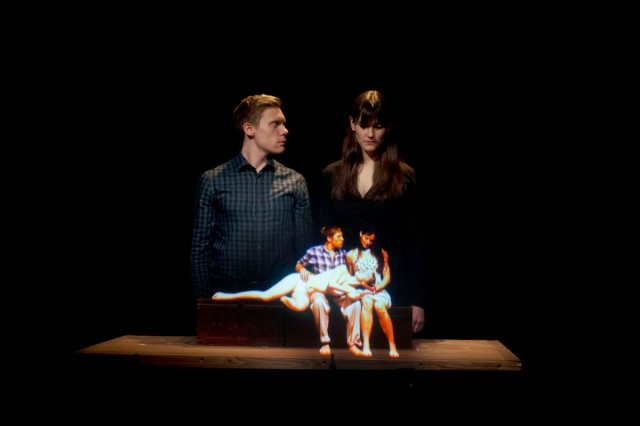 Two dancers, a man and a woman, look at tiny hologram versions of themselves on a table; a production show from Toujours Et Pres de Moi