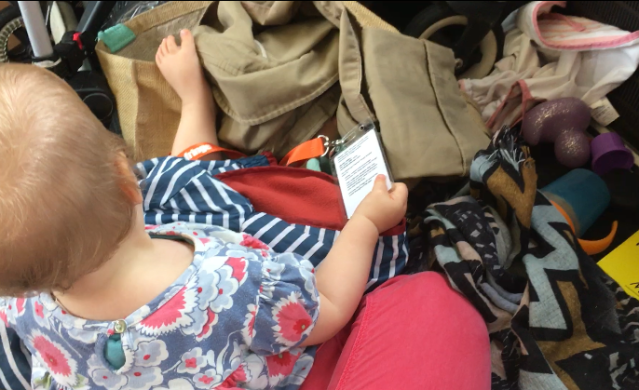 A baby sits amid a pile clothes and toys