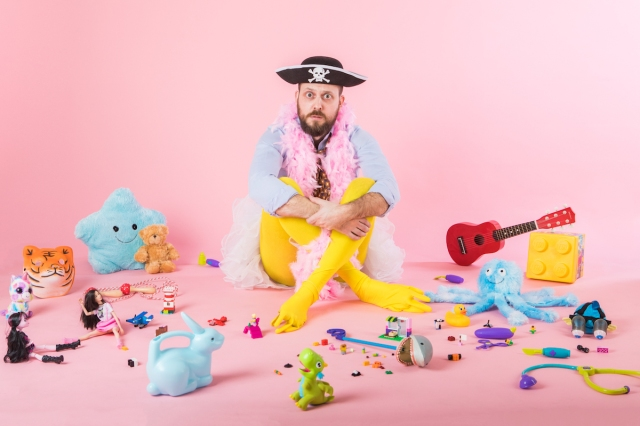 Comedian Owen Roberts wears silly clothes, surrounded by toys in a pink room, advertising his new show at the Edinburgh Festival Fringe © Ben Carpenter