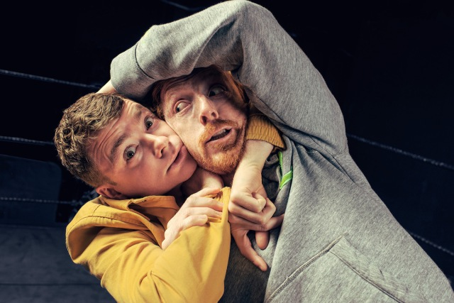 Publicity shot for Square Go: two actors have each other in headlocks