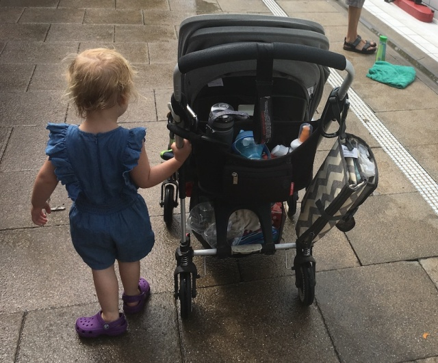 The toddlers walks beside a laden pushchair