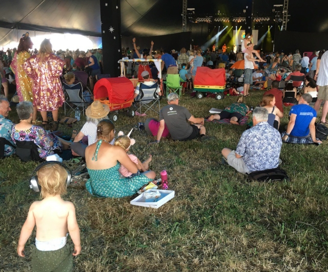 A toddler wearing ear defenders watches a gig in a tent at WOMAD Festival
