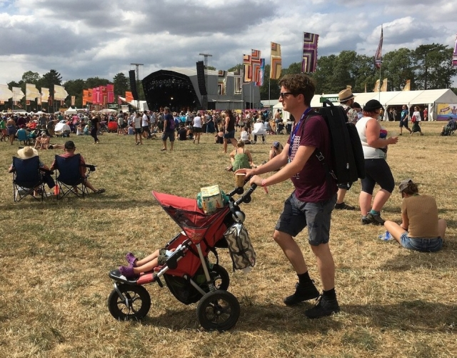 A man pushes a child in a pushchair at WOMAD Festival