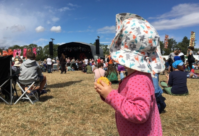 A toddler in a sun hat eats corn at a gig at WOMAD Festival