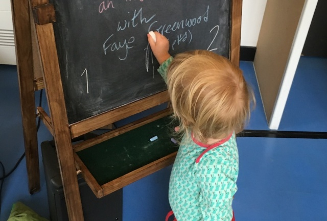 A toddler writes on a blackboard after the end of Shhh... The Elves are Very Shy at the Edinburgh Fringe